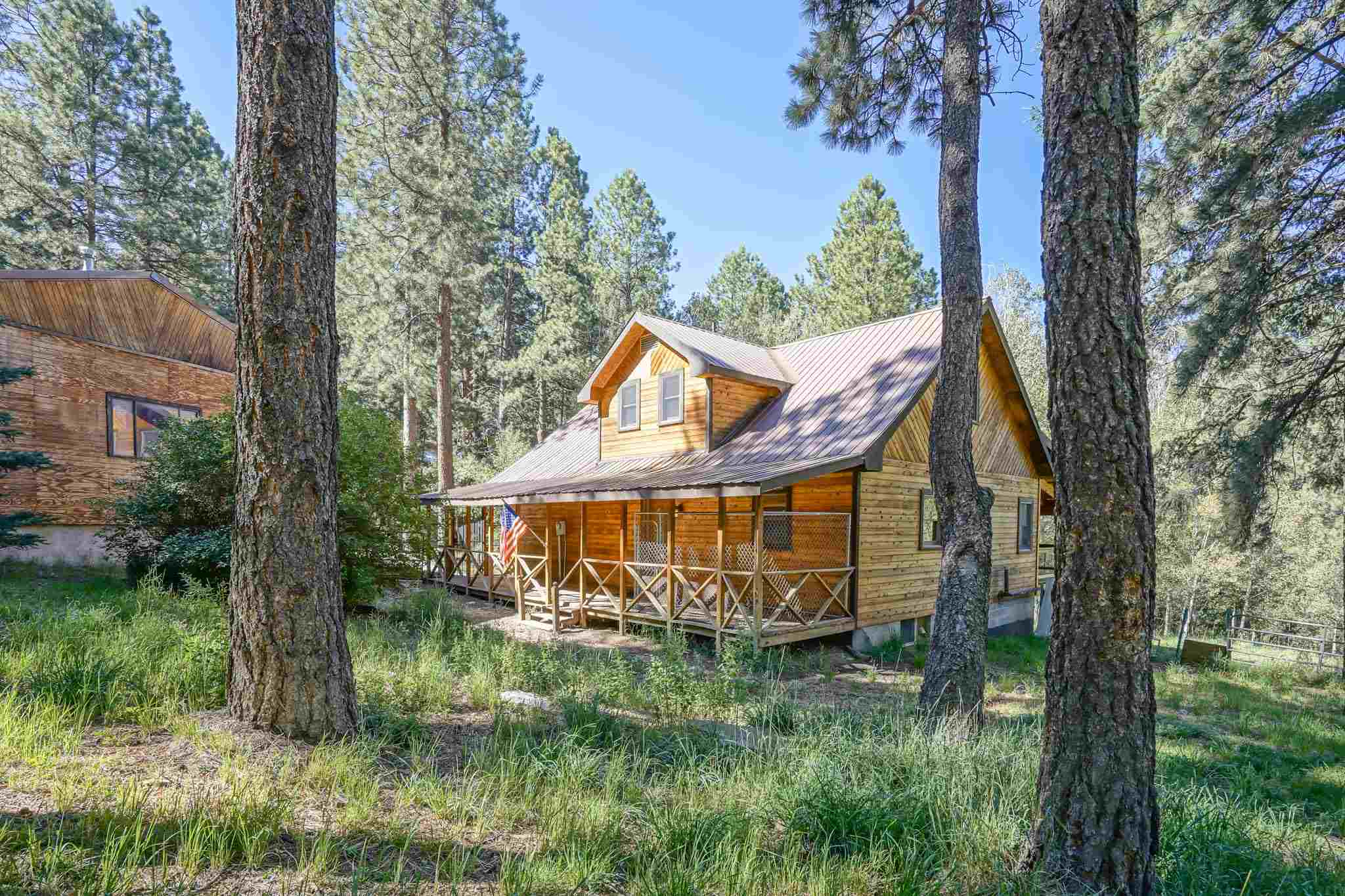 Ever imagine living on 1.4 picturesque acres in your very own mountain retreat with ''those'' views? Dream no more! This move-in ready home has it all, 1400sq.ft. beautiful decks perfect for outdoor dining. Relax and breathe in sweet mountain air, watch the wildlife or, entertain. Just a short 3/4 mi. hike to the Jemez river for fishing, cooling off in the falls. Ride out access to OHV trails. After a day outdoors, come home to your relaxing spacious yet cozy, retreat. Lovely wood floors, inviting wood stove, three bedrooms. Work from home in the large study. Transform this 1200 sq.ft. walkout basement into what you've dreamed; game room, theatre? There's a 1000 square foot shop large enough for the RV. Only a 25 minute commute to Los Alamos! Escape to the mountains, live the dream!!