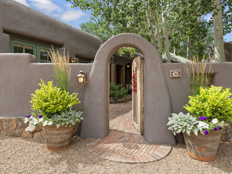 This fine residence in San Antonio Compound is The Best Location in Santa Fe - Close to everything but quietly tucked away off Acequia Madre.  Three Bedroom / Two Bath Adobe & frame construction, by respected Builder Jay Parks, has never been offered for sale & blends timeless Santa Fe charm w/ modern amenities. Seven Fireplaces, hand-troweled plaster walls, coved ceilings w/ vigas, beams & corbels, arched doorways, nichos, rustic antique doors, skylights, tile & hardwood floors (no carpet), A/C, radiant in-floor heat AND Two-Car Attached Garage w/ ample guest parking - Extremely rare on the Historic East Side.   Great Room includes impressive fireplace & access to covered back portal area w/ its own fireplace & room for entertaining. Kitchen offers top-of-the-line stainless appliances, cozy corner fireplace and casual dining area w/ French doors to the front entry courtyard w/ fountain, fireplace & BBQ . Master Bedroom includes a retreat area, en-suite bath w/ walk-in closet & access to back portal area. Two Guest Bedrooms are separated from the Master for privacy.   This home has it all -- Location, Adobe Construction plus Santa Fe style with modern amenities.