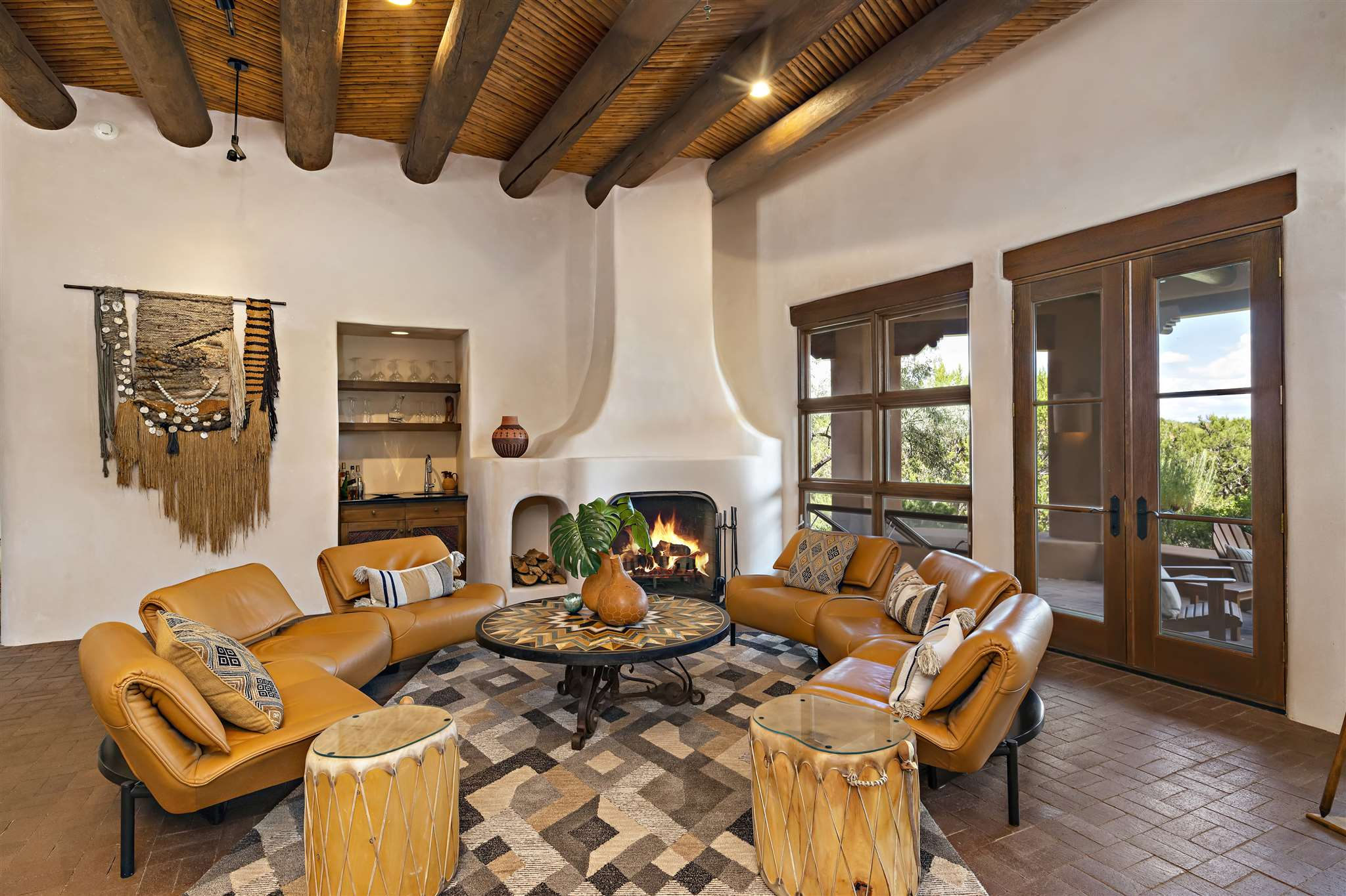 Transitional / Soft Contemporary home in Gated Las Campanas has it all -- Sangre de Cristo Views, 3 Bedrooms + Office, 3 ½ Baths, 3-Car Garage, In-ground Spa/Hot Tub & Spacious Roof Deck to take in the expansive 360-degree views. Great Room includes an area w/ a TV & Kiva Fireplace as well as another conversation area w/ an equally impressive Kiva Fireplace, Wet Bar plus a Sangre de Cristo view. Dining area can accommodate a large round or octagonal table w/ up to 8 chairs. Kitchen offers a Sub-Zero refrigerator, Bosch Dishwasher, Dacor Gas Cooktop & Ovens plus Butler's Pantry & Wine Cellar. Kitchen island has Prep Sink & built-in Buffet area to create ample counter & storage space. Master Bedroom includes a Kiva Fireplace, Spacious Walk-in Closet, Access to a private portal area & private retreat for reading or contemplation. Master & Office have refrigerated A/C. Master Bath offers separate sinks, two separate compartmented toilets, new shower with body sprays & direct access to the Spa / Hot Tub & Outdoor Shower. Two secondary bedrooms are located on the opposite side of the home for privacy from the Master, each with their own baths. Outdoors has a multitude of desirable features - Private In-Ground, Spa/Hot Tub, Outdoor Shower, Built-in BBQ , Expansive Roof Deck & Shaded Portal area w/ Outdoor Fireplace to warm the evening air. This fabulous home offers Views, a multitude of desirable features & is in Move-in Ready, making it the perfect residence in Las Campanas.