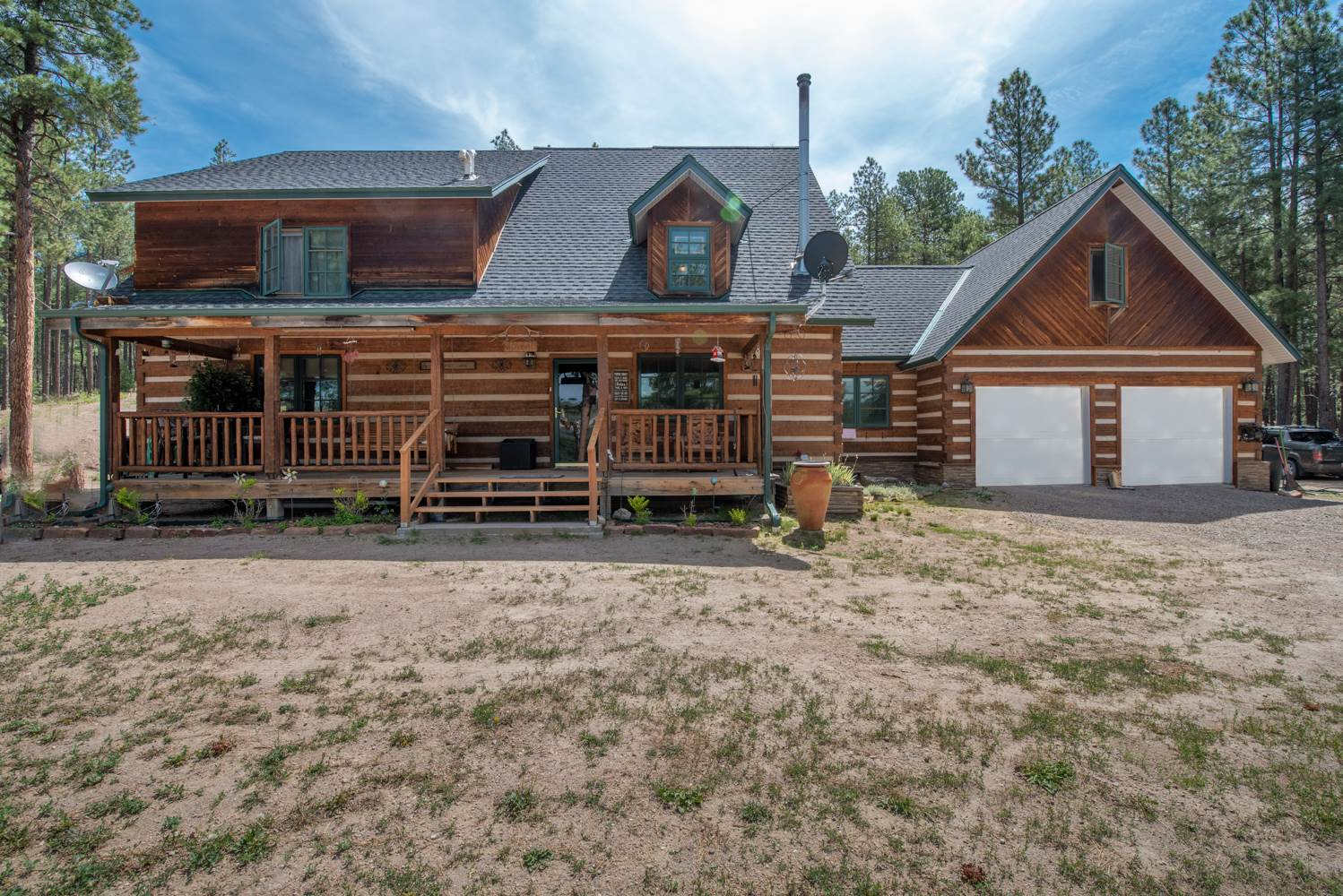 Beautiful setting for this home built with Northern Hemlock logs on 2 acres of land among soaring Ponderosa Pines. Enjoy the mountain air from your 8x24' covered front porch looking out to the mountain range. Great rm w/ Wood stove, vaulted ceilings, a 26ft pitch,  wood beams. Functional kitchen, stainless appliances, ample counter and cabinet space. 2 bedrooms and a bonus/flex room that could be an office/recreation/fitness on main level. Upstairs offers a loft and a spacious Master suite, huge walk in closet, bath w/jetted tub, separate shower. Viewing deck off Master. From lower level access back yard with SW landscape, privacy fence and hot tub. Also access to a separate entrance for in laws quarters/studio apt. complete with kitchenette and bath. Horses allowed, w/RUN IN stall and storage shed. Room for RV. Short drive of Los Alamos National Labs, Jemez Springs, and all the outdoor recreation the Jemez Valley has to offer.  Mountain Living at its finest