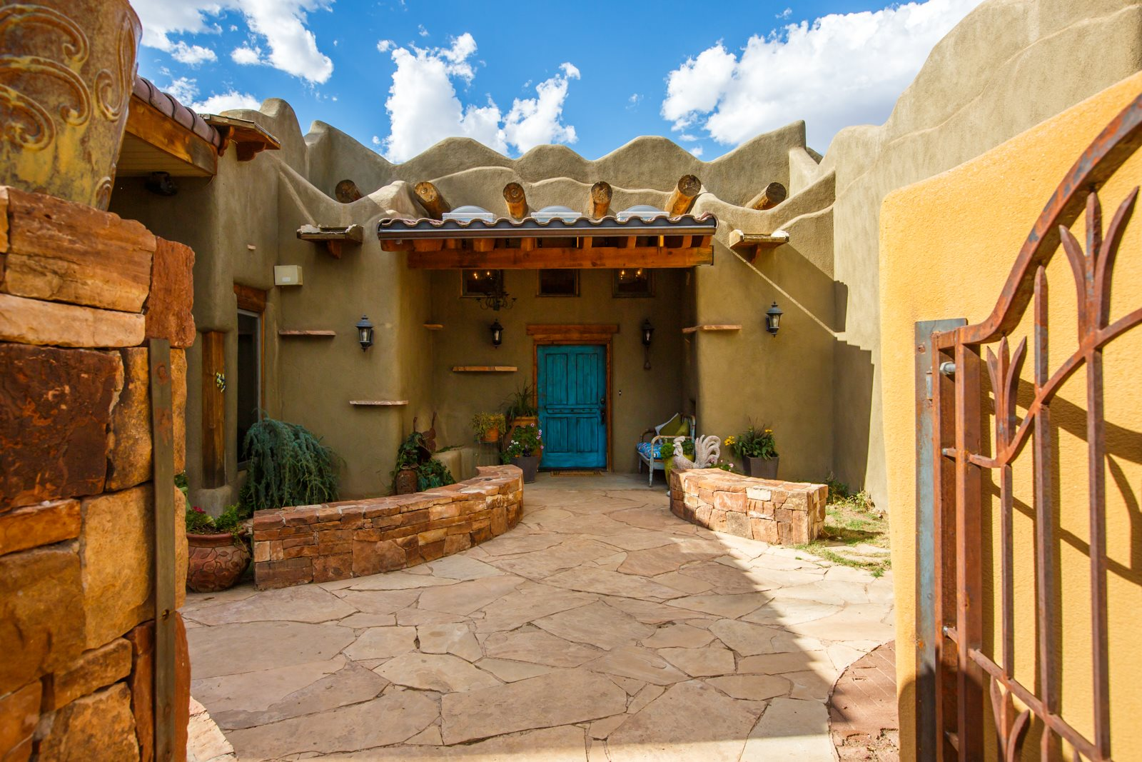 Love the artistic, colorful flair of classic Santa Fe/Taos adobe luxury architecture, but prefer something more centrally located in the Land of Enchantment? In the North Valley's Los Ranchos de Albuquerque, on a full acre of irrigated land along Rio Grande Blvd, this custom, one-of-a kind home and its guardian lizard await you. Walk through the partially covered courtyard, and upon entry to the home you get a sense of spaciousness, whimsy, and Southwest artistry, in the high Viga, Latilla, and Hammered Beam ceilings, exposed adobe and diamond plaster walls, artistic mosaics, and stone floor. Multiple living spaces, indoor and out, make it easy for generations to live together. The loft wing has a separate entrance for a studio, office, or, with a bedroom, bath, living space, and room to add a kitchenette, it could be private living quarters for parents, teens, or adult children starting out. This adobe home is efficient, with radiant in floor heat, and refrigerated air to complement passive nighttime cooling. The garage and workshop, with a half bath, and rooftop deck access for enjoying the night sky or balloons in flight, complete the home. Want more? There's plenty of room to add a pool, barn or both! Come home to the central Rio Grande Valley where you can get more for less and still enjoy the quality and style you expect from a classic Northern New Mexico adobe home.