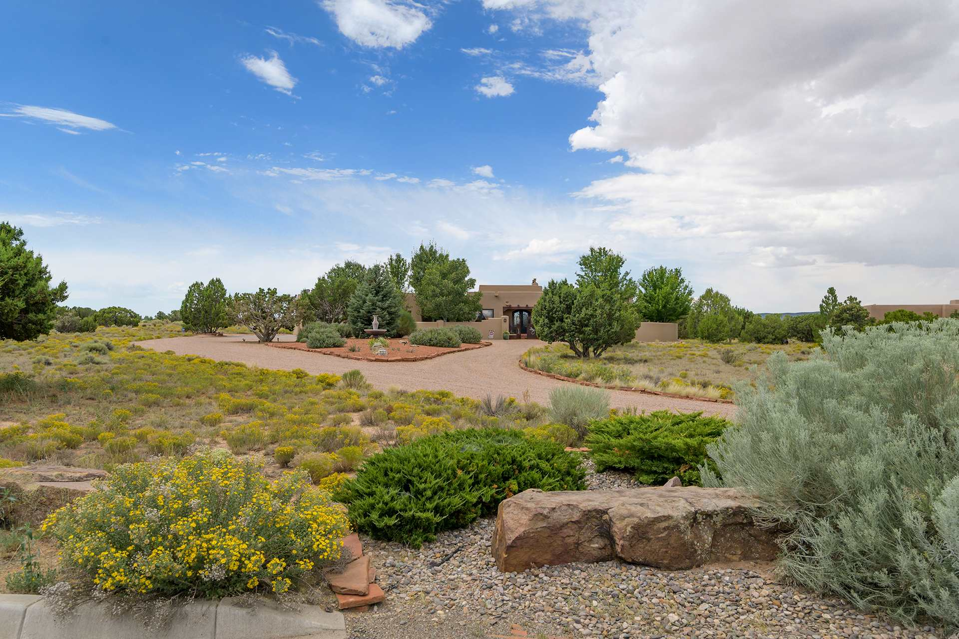 In the market for serenity? Want that spectacular sunrise and sunset? Sit back and take in the stunning big sky views of the Jemez and Sangre de Cristos from this single level custom home. Conveniently located in the lovely gated community of La Villa Escondida, you are just minutes from the plaza and easy access to 599.  This equestrian property is nestled on 2.92 acres. Built with energy efficient Rastra construction, custom details are everywhere.  The circular drives leads to a grand gated entry into the professionally landscaped courtyard. Step into the entry foyer and take in the mountain views from the spacious great room and formal dining room.  The hand troweled plaster walls, stone floors along with high ceilings, vigas and nichos make a quality statement. The grand chef's kitchen beckons with granite countertops, top of the line appliances and walk-in pantry. Settle into the dining alcove which opens to a private covered portal with a fireplace. The perfect spot for alfresco dining. The split floor plan features a grand master suite along with a guest wing ensuring privacy. The master suite has a cozy kiva fireplace, luxurious spa bath, large walk in closet and access to a covered portal. The guest wing features two guest bedrooms with en-suite baths plus a multi- purpose bonus room with fireplace that could easily  be  a den or superior home office.  The attached 3 car garage with work space completes the amenities in this special home.
