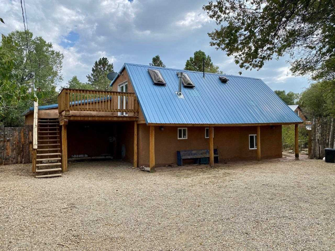 TAOS TRUE- It's the real thing.  The one-story main home of this property is a triple thick adobe with a 1,574 sq.ft. 2BR/2BA adobe home with flex space for library or office, plus a separate 1BR/1BA casita upstairs.  With parts rumored to be over 100yrs old, it was tastefully remodeled in 2007-8 to retain its old world feel yet updated for today.  The thick, smooth walls w/ hand troweled diamond finish plaster throughout. There are viga ceilings and wood plank floors through most of the house for that Taos ambiance. The indoor spaces flow to the huge hacienda style portal which graces the front and entrance and provides places for dining al fresco and  having a socially distanced happy hour with friends all in a serene natural setting. The living room boasts a delightful and efficient Jotul gas log stove and the adjoining flex room could be used for media, a library/office, or formal dining room.  The kitchen is spacious and bright and large enough for a dining table and has granite countertops and stainless appliances.  Out the kitchen is another portal and a fenced area for pets.  Upstairs you'll find the sweet, bright and light 1BR/1BA casita with full kitchen and W/D.  Enjoy the deck for star gazing or lazing.  The yard has perennials and a dry creek bed and fountain that can be restored and there's room for gardening.  Nat'l gas and community water & sewer.  This property provides lots of options.  Short or long term rentals, home/office, house/guesthouse.  You choose.