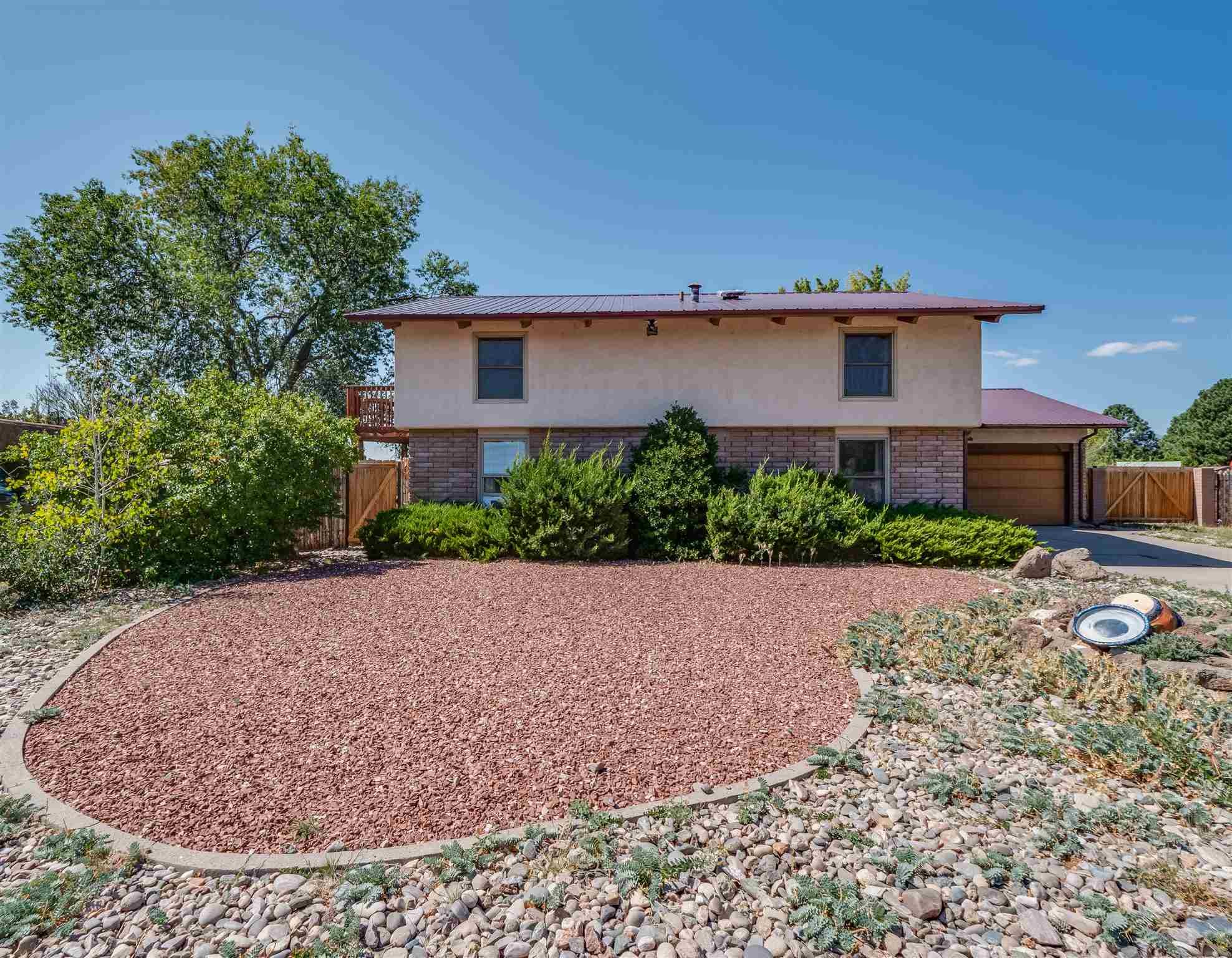 Located on a spacious 0.46 acre lot in a cul-de-sac, this property is not to be overlooked! This home offers a fully fenced backyard with views of the Jemez in addition to a wonderful covered patio space with a high ceiling. A deck can be accessed off the patio as well as from the loft space in the home. From the deck, enjoy nice views of the Sangres to the east extending around to mesas at the south and back to the Jemez in the west. Inside offers an open living space accented by vaulted ceilings and wood beams as well as a wood burning fireplace with built-in wood storage all complemented by rock. Lots of natural light and nice views out back pour in through high windows and impressive three panel slider door to the patio. The living space is open to the dining area which flows into the kitchen. Impressive custom kitchen with stainless appliances including Wolf range and hood and Viking refrigerator. Attractive and ample cabinetry is accented by granite countertops and tile backsplash. Just off the kitchen is a large laundry space with great storage cabinetry and outdoor access. Updated laminate flooring flows throughout the living spaces while tile flooring is found in the kitchen, laundry, and bathrooms. Two versatile guest rooms are located on the main floor with a large guest bath located between. Upstairs leads to an open loft with built-in shelving and French doors to the deck. An additional bedroom upstairs connects to a neat bonus space with full bath nearby.