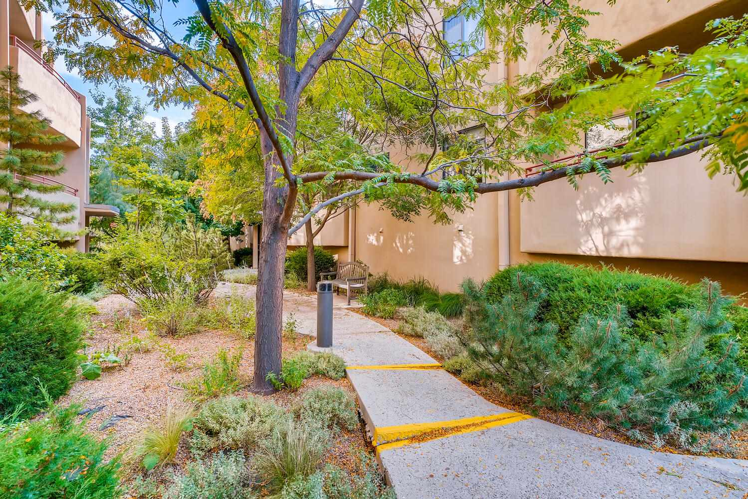 Urban oasis surrounded by mature trees!  Superb midtown location perfect for walking, bicycling or catching the train.  Close to restaurants and shopping and anything you need.  Upscale and mildly contemporary condo with 2 balconies overlooking lots of greenery.  Some views of the Jemez mountains and colorful, magnificent sunsets. Light filled, open and very comfortable floor plan with a large and exciting kitchen that includes stone counters and substantial cabinet space including a spacious pantry.  The warm, hardwood flooring adds additional beauty and dimension to the home.  Spacious living area lends itself well to a variety of layouts.  Two comfortable bedrooms and a large bathroom with room for two and centrally located utility room. Surprisingly large 6.50' x 17' personal storage unit for seasonal items and sports equipment.  Covered parking for your car close to the home. Beautifully inviting landscaped entry and walkways.  Very private and quiet location.
