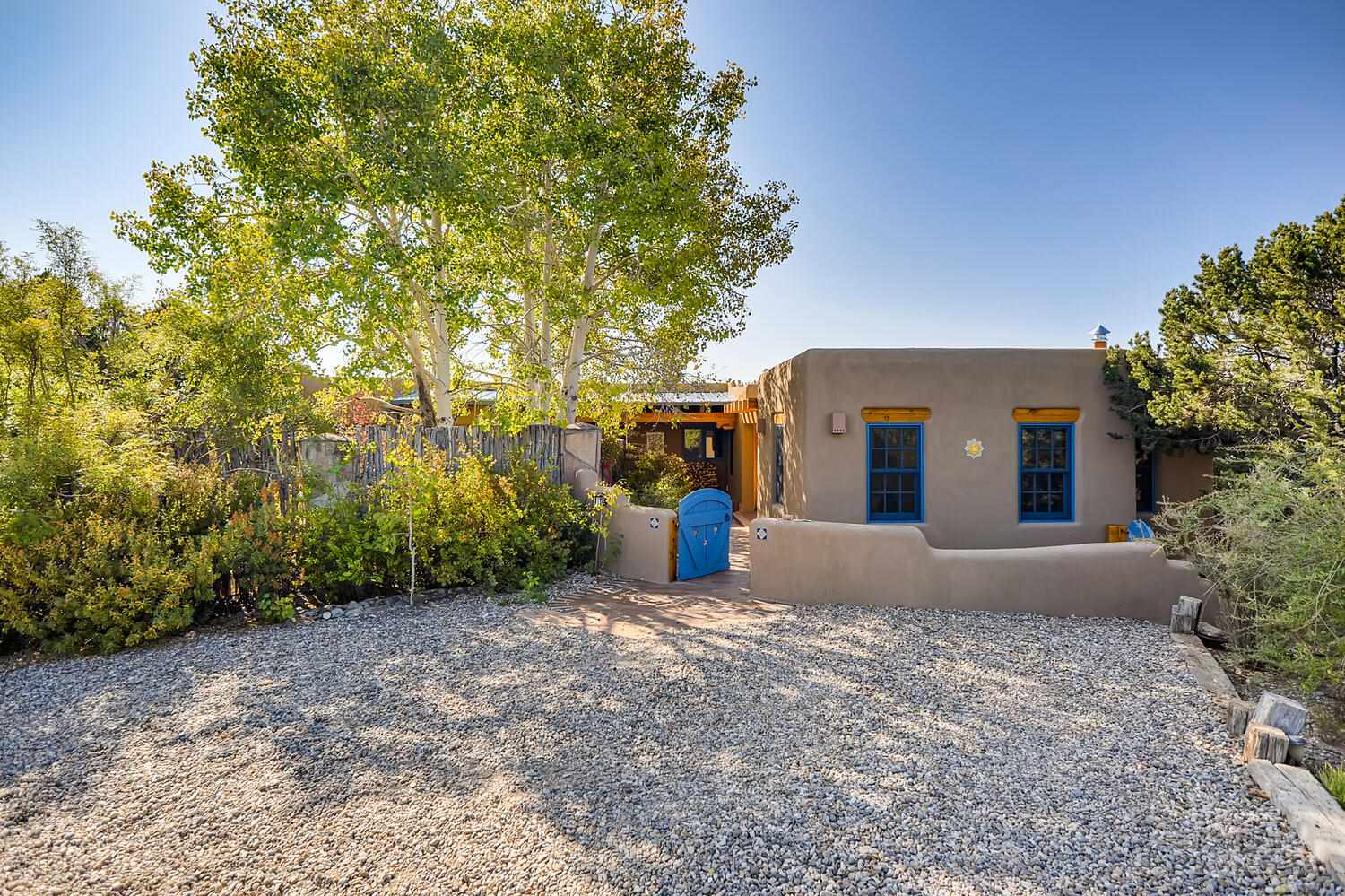 Big dramatic views of the Sangres and Jemez Mtns. The entrance is gated.The house and guest house were remodeled and expanded in 2015 ,the 300sf passive solar studio/workshop was built in 2017.The property offers 3.6 private, beautifully treed acres. The main home offers 2bds, 2 bths, a newly built office, family rm, pantry and nook.The guest house offers1 bd 1 bth. There is a 2 car garage and carport.Living spaces are heated and cooled by mini splits.The main house has tile floors, wood ceilings, 3 fireplaces, customdoors, cabinets, shelves, nichos, bancos, skylights and views from every room. A brick entry, 2 decks, flagstone terrace, in groundwater feature, and walled garden surround it. The living room and master have Sangre views The open dining and sunrooms are filled with light. The kitchen with all newer appliances has cabinets painted by a local artist. The remodeled bathrooms have artistic tilesand a steam shower.The charming guest house has tile floors, wood ceilings, custom cabinets, full bath, BIG Sangre views and a covered deck. The 2 car garage with laundry is attached. The passive solar studio/workshop is light-filled with a wood stove and electric back up. There are 2 custombuilt storage sheds. This amazing property is10 minutes to downtown Santa Fe and an easy commute to Los Alamos.