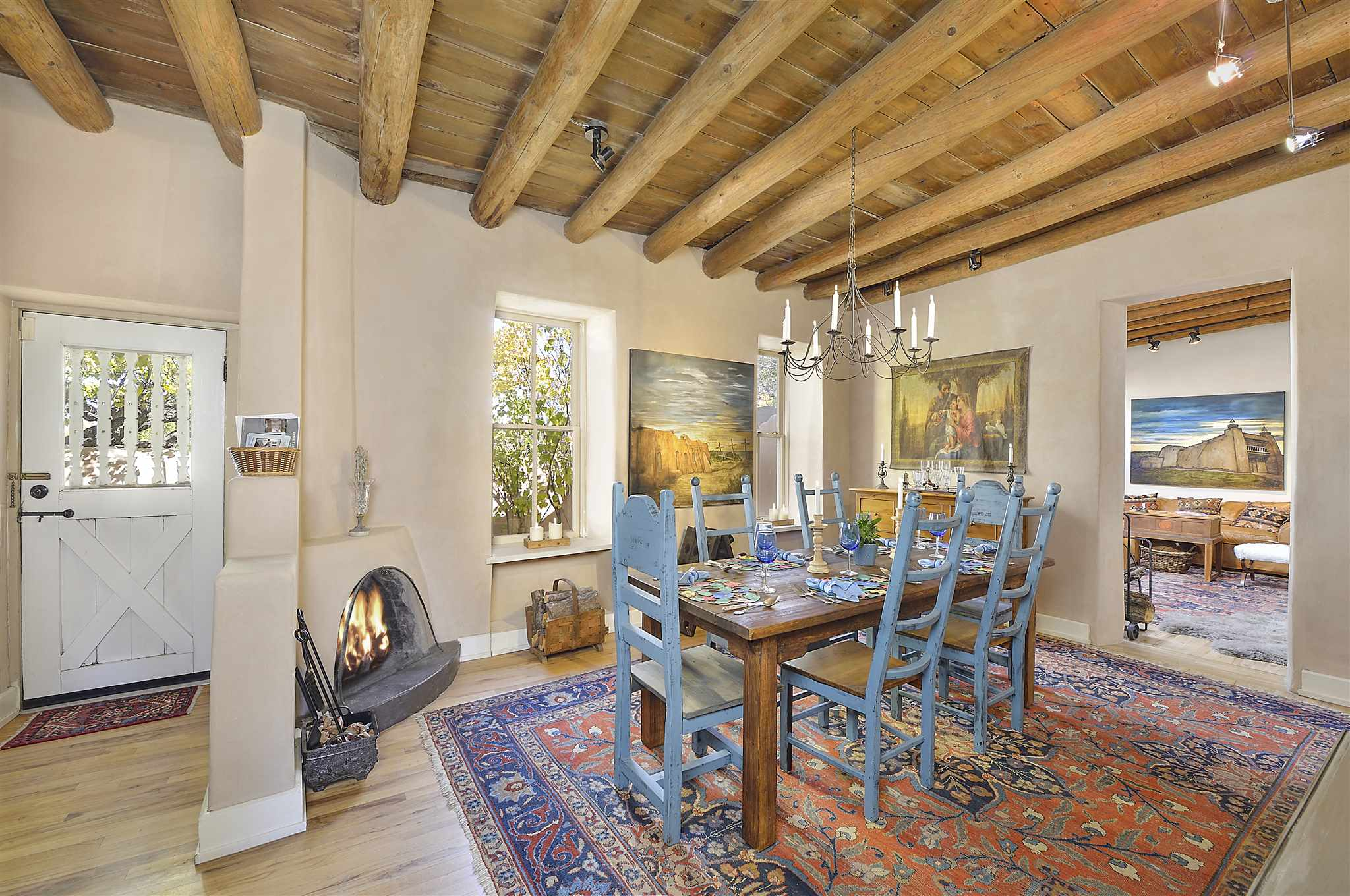 Recently renovated 3 bedroom 2 bathroom condo tucked away near downtown Santa Fe on the Historic Eastside. Private, brick-lined courtyard with rustic hand-carved wood gate and covered portal. The character and history of the Southwest flow into the living room with viga ceilings, wood floors, and a kiva fireplace, one of five kivas in the home. The renovated kitchen is appointed with custom wood cabinetry, butcherblock countertops, recently added stainless steel appliances, and an intimate breakfast nook. Split bedroom plan with two adjoining bedrooms on one side of the home with a third bedroom or multi-flex space on the other. Extra closet space recently added and laundry room reconfigured. The bathrooms feature subway tile throughout, porcelain vanity, and tub and shower combo. Wood floors throughout. Private brick-lined front courtyard, covered storage, 1 car garage and 3 carport parking spaces. Perfect pied-a terre or investment opportunity. Close to the state capitol, Canyon Road and the Plaza.