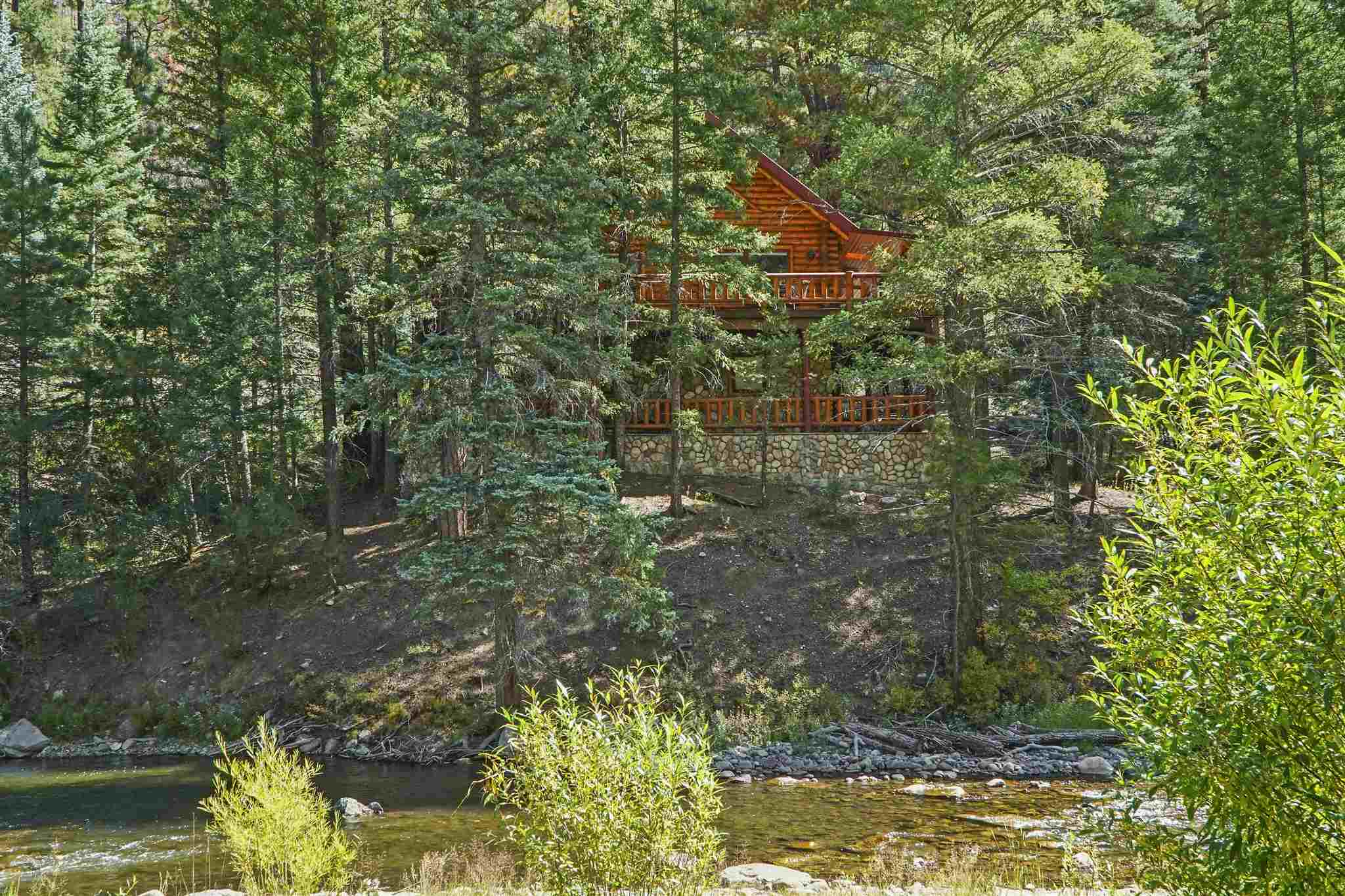 Rare offering of one of the most privately sited cabins in Tres and close proximity to the Santa Fe National Forest. This beautiful log cabin is perched above the river and tucked into the towering pines. Enjoy the sounds and sights of the mountains from within or from the covered and open wraparound deck. The main level features open concept dining, living and kitchen with a stone faced, wood-burning fireplace, spacious guest bedroom and three quarter bathroom. Upstairs is reserved for the master suite with a luxurious master bathroom and two small balconies to enjoy the crisp mountain air. The lower level, walk out basement features a bunk bedroom with a full bathroom, plus a fly fishing staging area, perfect for putting on waders and heading out to fish! Tres Lagunas offers private water fly fishing exclusive to owners and their guests, over one third of a mile of the Pecos River, 3 stocked ponds, on-site caretakers, all make for a wonderful retreat less than an hour from Santa Fe.