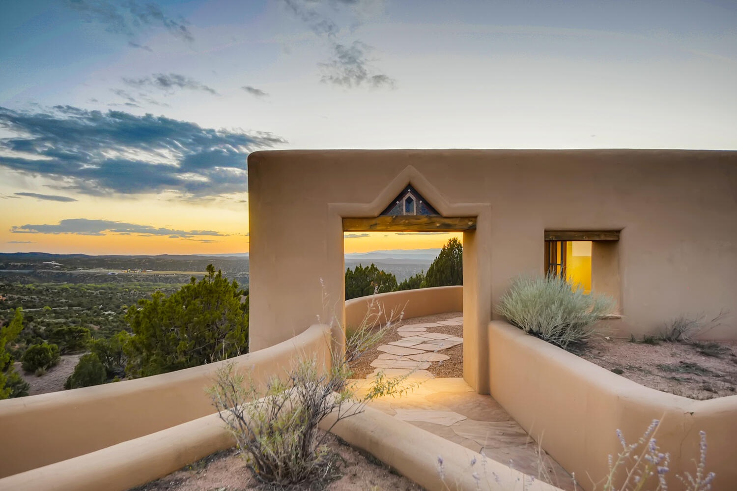 This stunning Ken Mackenzie masterpiece boasts million dollar views of Sangres to the east and the vast Jemez to the west and north! Incredible architectural details paired with fine indigenous stone, wood and plaster finishes make this home a one of a kind along with its intense 360 views. This property will take your breath away! Every window has a picture to show you and as you open the garage door looking out – there are views! Every detail inside is a hidden surprise. You will find yourself in awe not only with the views but with the interior as well.  A beautiful custom kitchen and dining area open to the living room that flaunts large picture windows, French doors leading to the patio and a show stopping fireplace. There are two sets of impressive double doors that lead you to the master suite and master bath with a separate shower and tub – there is even a window to look out of while soaking. The guest wing has a ¾ bath an office/den/ or 3rd bedroom. There are so many details to this amazing property - it should be experienced in person. Schedule your private showing today. You might just wish you brought a bottle of wine as you sit on the beautiful patio enjoying the show.