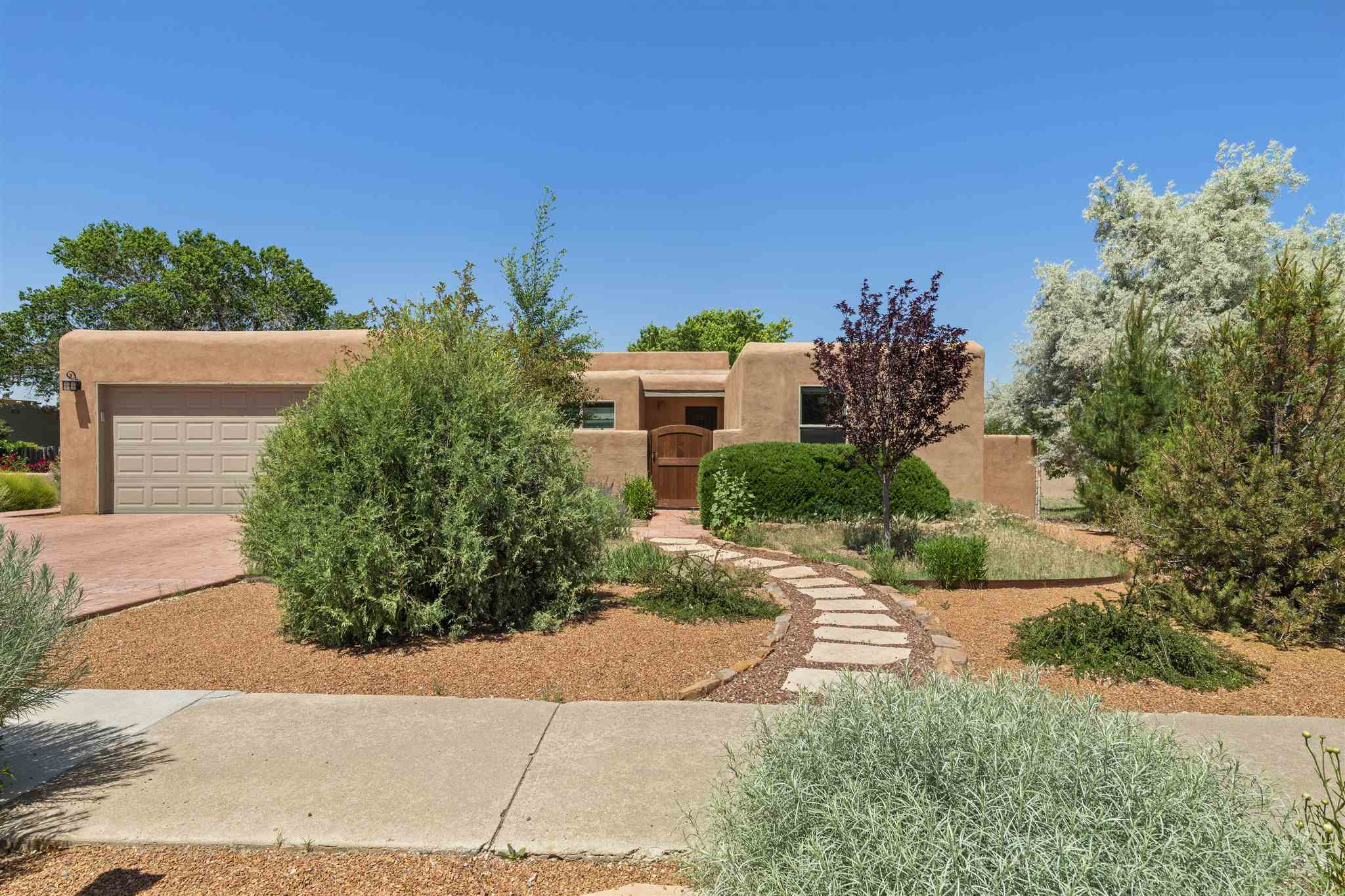 This home has been extensively remodeled, beginning in 2017 with new windows, new stucco, updated guest bathroom, and wrap-around deck opening off the west-facing sunroom. The current owners have spent more than $200,000 on additional improvements since then. These include a true chef's kitchen with custom cabinetry featuring uniquely functional drawers and shelves, quartz countertops, wall oven and microwave, new stainless steel appliances, reverse-osmosis filtration, skylights, and new custom lighting. The induction cooktop on the huge island responds instantly like gas. The master en-suite bath was also completely redone, including a walk-in shower, custom two-sink vanity, and new floor tiling and custom lighting. A brick floor was installed to replace carpeting in all common areas and the master bedroom. Skylights and a built-in bookcase were added in the living room. A new front-load washer and dryer set was added, as well as a new furnace and tankless water heater. A $50,000+ investment in extensive, professionally designed and installed landscaping in both the front and fully fenced back yard includes an irrigation system, fruit trees, lush flowering plants, new flagstone courtyard patio with water feature, new gates, and new driveway and walkway. Ideal in-town location, quiet and convenient. An unexpected relocation makes all this available to you!