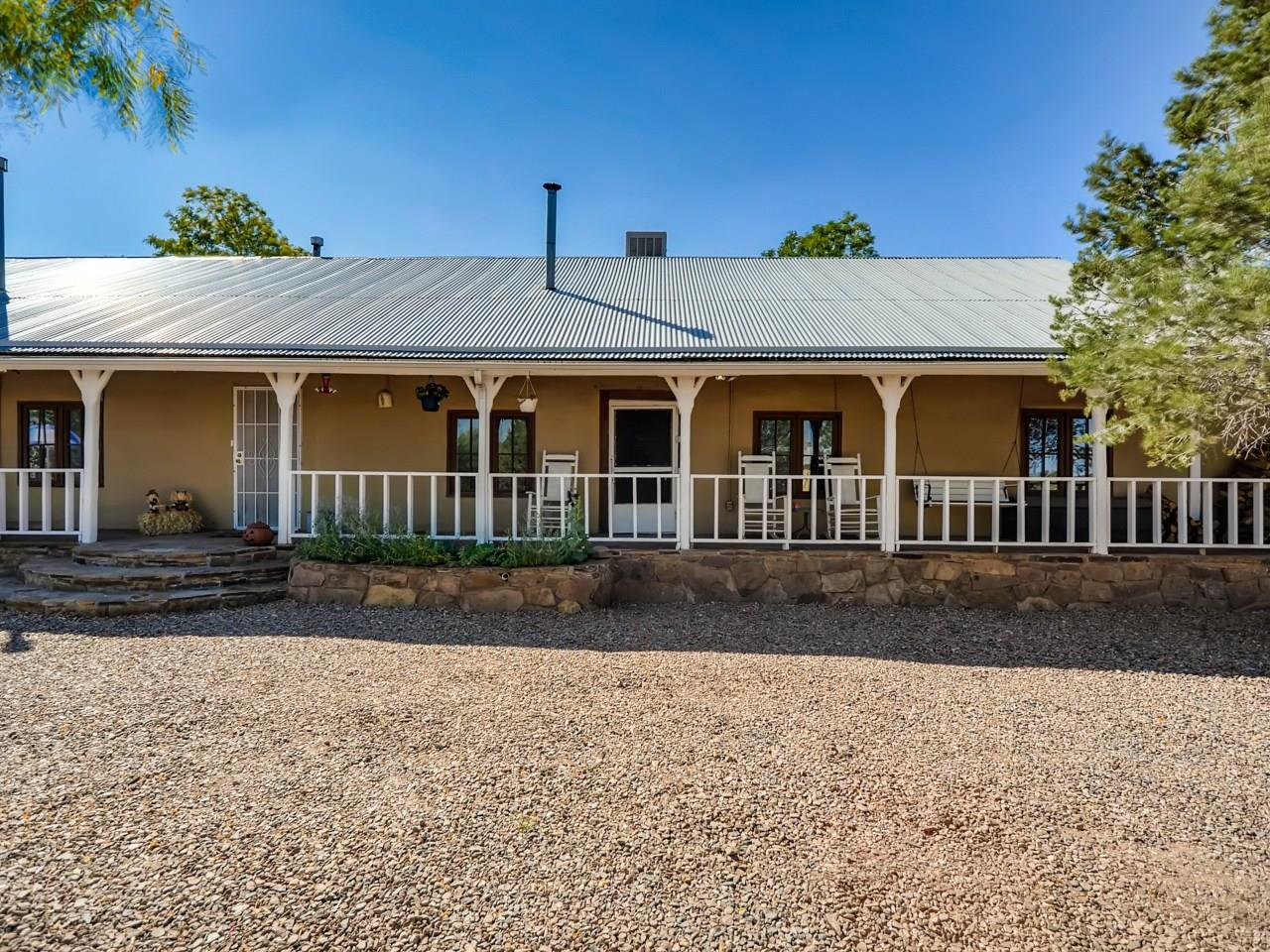 Genuine Adobe Hacienda Compound overlooking the historic church accessed by Route 66 & the Santa Fe Trail offering a variety of options with 2 legal lots of record. The 5039 +/-sf. main adobe home, partially built in the mid 1800's has 4 beds, 2 baths,5 fireplaces/stoves. Many of the walls are over 2 feet thick, portions of the structure, were the local mercantile store/post office. Scenes from movies All the Pretty Horses & Hi-Low Country were filmed at the property. Adobe rooms have served as office, music room, den, dining room, & living room.  Along with the historic grainery, there are 1366 +/- sf of covered portals, a garage and over 600 sf of storage area.  The 762 +/-sf. guest/apartment located to the east of the main house with bedroom, 2 ¾ baths, living/kitchen combo has offered rental income.  Just across the back courtyard, is the 454 +/-sf. shop/studio w/updated electric, tall ceilings & cement floor. Next to this building is a 249 +/-sf. adobe artist studio w/vigas. The 2nd lot, adjoined and across County Road B-41 C contains the Equestrian components.  An open 1934 +/-sf. barn with tall ceilings and double doors can accommodate a large number of horses. The 718 +/-sf. loafing shed w/metal piping contains 5 covered stalls, open areas and branding station. The 298 +/-sf. Tack room w/wood burning stove is a great spot after riding miles on adjoining BLM open land. A short distance to Pecos River, 40 minutes to Santa Fe 25 to Las Vegas.