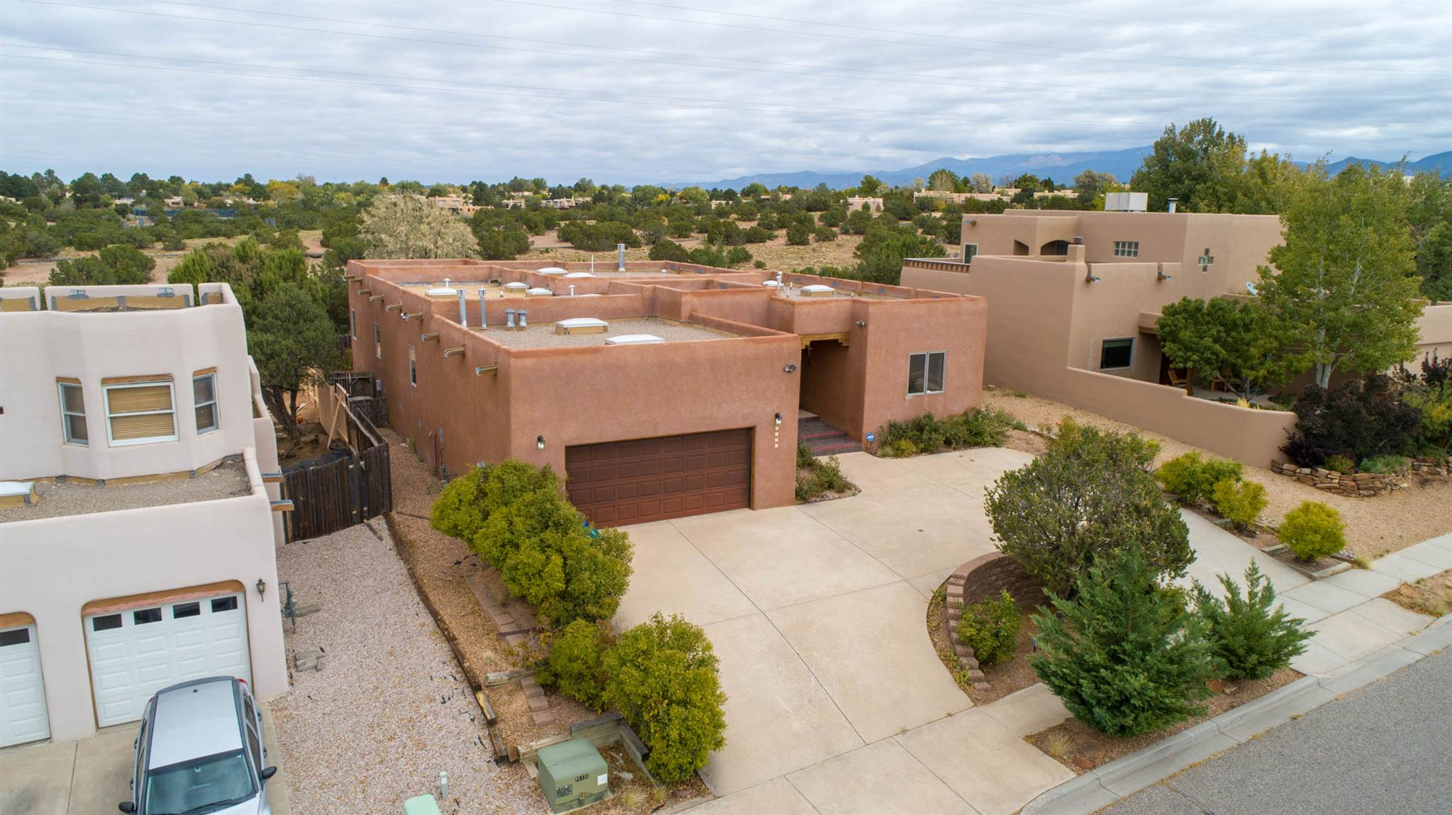 Single Level Floor Plan, in the coveted Pueblos del Sol neighborhood that borders greenspace. Wood ceilings beckon you into this thoughtfully designed home that creates the perfect place to entertain. You will find a wet bar with a mini fridge, powder room, gas fireplace flanked by view windows, bancos, a multitude of kitchen cabinets, a prep sink, and a breakfast area that leads to an expansive portal to take in the spectacular Sangre views. Featuring plantation shutters, central Air Conditioning, ample storage, separate dining room with built in cabinetry, and a family room/office with portal entry. Walking trails close by and minutes by car to all the south-side conveniences. About 10 minutes to the historic Santa Fe Plaza.