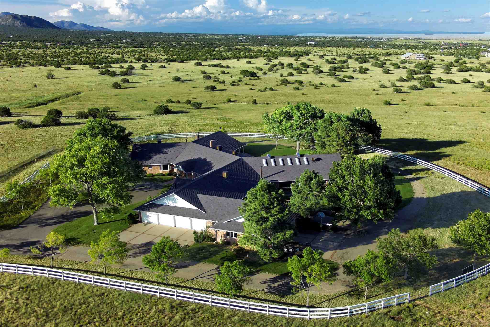 Where the mountains meet the Great Plains, this charming equestrian property know as The Starlight Ranch has captured the essence of the Wild West while elegantly merging beautiful detailing and a thoughtful floor plan in this one-of-a-kind Bob Coe home. Situated next to the San Pedro Mountains just on the outskirts of south Santa Fe county, the entire property encompasses 85 completely fenced acres which include an 11,900 sq.ft. single-level bricked home with 7 heated, direct entry garages and 2 carports. Features include evaporative cooling, zoned baseboard heating, natural gas, new electric solar panels, fiber high-speed internet, 2 septic systems, central vacuum, and a gated entry with a whole-house security system in place. A heated, indoor upgraded 20'x40' Gunite pool with additional kitchen/serving facilities and entertaining spaces is centered in between the kitchen, game room, and living spaces. Just behind the property is lovely pasture land, a riding area, and a 4-stall BarnMaster metal barn with a center aisle and turnouts-equipped with water and electricity. Vistas of the nearby San Pedro Mountain, valley and Sandia mountain range just miles from the Turquoise National Scenic Byway, can be admired from most living and bedroom spaces, as well as from over 1,700 sq.ft. of patio and outdoor entertaining areas.  (continued below)