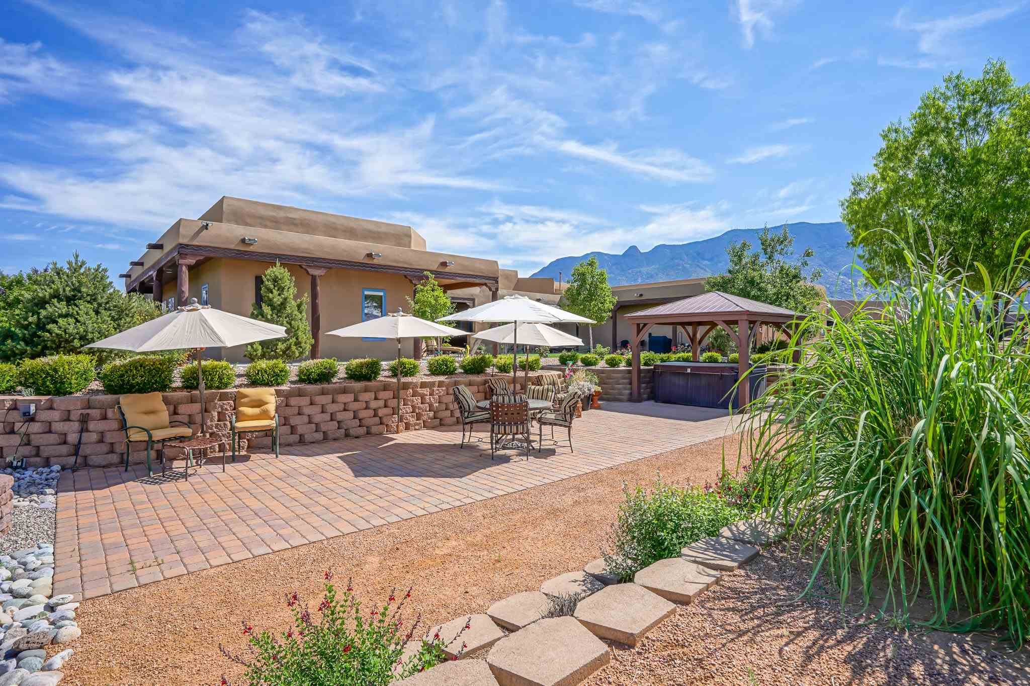 Open House Sun 2/21 1- 3 pm. Gracious Classic Santa Fe Style Hacienda on .89 North Abq Acres. Whole casa warm brick radiant heated floors,4 Kiva fireplaces, 5 bdrms, 3+ car garage, Pella wood windows, artisan woodwork, hand carved doors & posts, furniture quality handcrafted soft close dovetail cabinetry, wide wood trim, silver finials. Owners retreat like none other: 2 way fireplace, attached den and exercise space, beamed ceiling, dbl sinks, jetted tub, travertine shower, walk-in closet. Fully appointed Chef's entertaining kitchen, pot filler, 4 Wolf ovens, 4 burners + griddle/grill, Sub-Zero Side by Sides, huge butler's pantry with built ins. Outdoor kitchen playground, Wolf grill, wood burning Kiva, TV, pergola covered spa. Balloon Fiesta Views! Cable/ethernet in every room + IT room