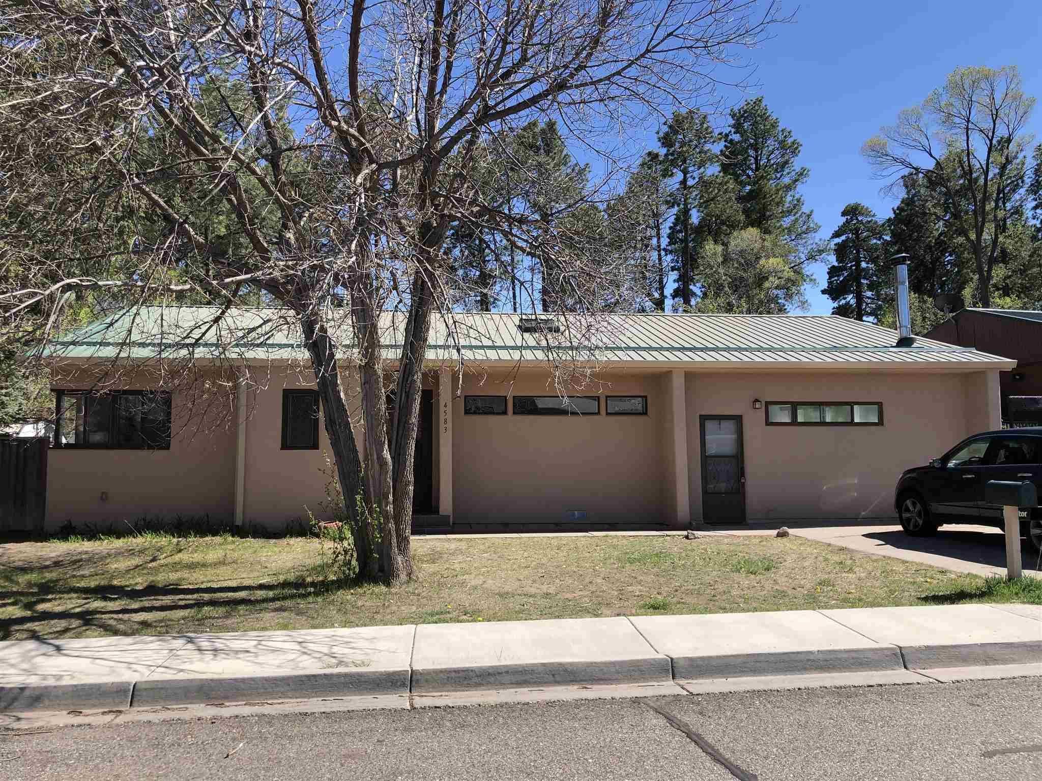 Come check out this sweet, move-in ready Western Area charmer! And looking for A/C? This home has a brand new central a/c with air scrubber/allergy reduction technology. The location of this property is fantastic! It is close to schools, parks, pools, trails, LAMC, LANL, and downtown. Western Area is a well established and highly regarded neighborhood. The property boasts a large, private, fenced and wooded back yard that is a blank slate; ready for you to design your own quiet, oasis. There are several fruit trees on the property There are also two sheds for storage. The pitched, metal roof has brand new gutters, and avalanche guards. The stucco is only a few years old and in great shape. Inside you'll find newly refinished-original solid hardwood floors in the living room, 2 bedrooms, dining room, and kitchen. The charming cottage kitchen is nicely a great workspace, and boasts 1-year old stainless steel appliances. The second living area has large windows, brick floors, and a wood burning stove. It's perfect as a year round space for relaxing. The home is full of open spaces, and lots of light. The large primary bedroom suite includes a wood stove, 3/4 bathroom, closet area and laundry with year old washer and dryer-this space also has income potential with it's own exterior entrance. On the other side of the house there are two large bedrooms, plus small office/storage room, and one full bath. The home has been well taken care of and is ready for you to enjoy!