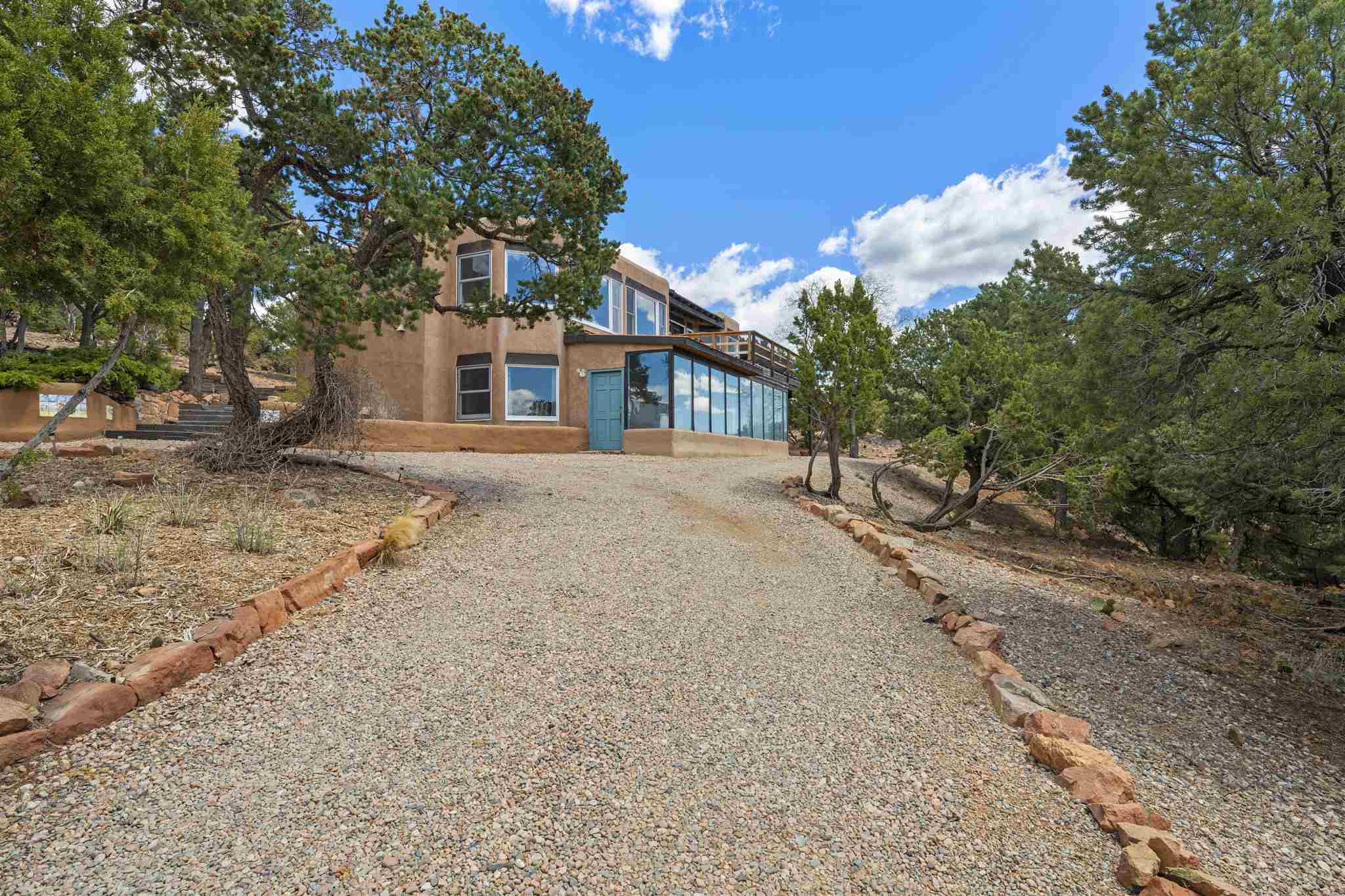 A rare 5-acre property located minutes from downtown Santa Fe, this multi-level home offers spectacular views at every turn. Tucked high in the hills, this former horse property allows for plenty of space to explore and take in the distinctive landscape. This property features classic Pueblo-style details of viga-and-plank ceilings, Saltillo tile floors and wood burning Kiva fireplaces.  A solarium below and sun deck on the upper level give opportunities to enjoy the views in any kind of weather.   Large picture windows on both levels of the home and a multiplicity of skylights provide ample natural light.  Formal and casual dining are both facilitated by a breakfast room set in a nook with bay windows and the adjoining dining room that accesses a porch that can be used for outdoor summer dining.  Three spacious bedrooms, a den with a wood-burning stove and office/study space are conducive to guest accommodations and/or family living.  A detached log cabin provides a storage option or opportunity for conversion into a guest cottage or studio.  Property has a private well.