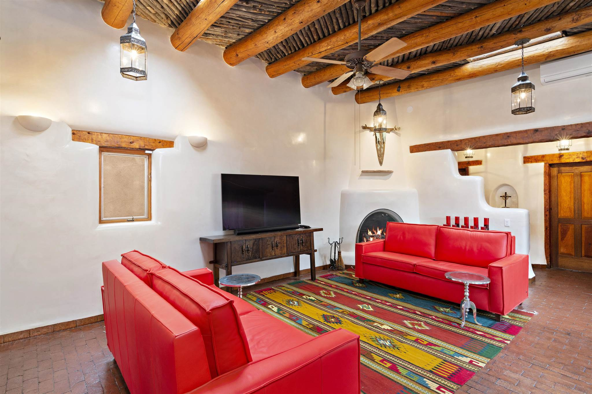 This condo is quintessential Santa Fe/Pueblo style with many recent upgrades. Brand new diamond finish plaster walls, custom carved wood details, high coved ceilings with vigas, and recently refinished brick floors. 2 bedrooms each with en-suite bathroom, open living room and dining room, and delightful Santa Fe style kitchen with sombraje cabinets. Recent upgrades include upgraded electrical wiring and outlets, 3 new mini-splits for heat and cooling, exterior and interior wood treatments, radon mitigation, and security system. Copper-based in-floor radiant heat to keep the house cozy in winter. Reserved carport parking for one car and plenty of on-street parking for guests. Walk to SantaCafe and the Plaza in only a few minutes! Gorgeous private patio with apricot tree and grapevines.