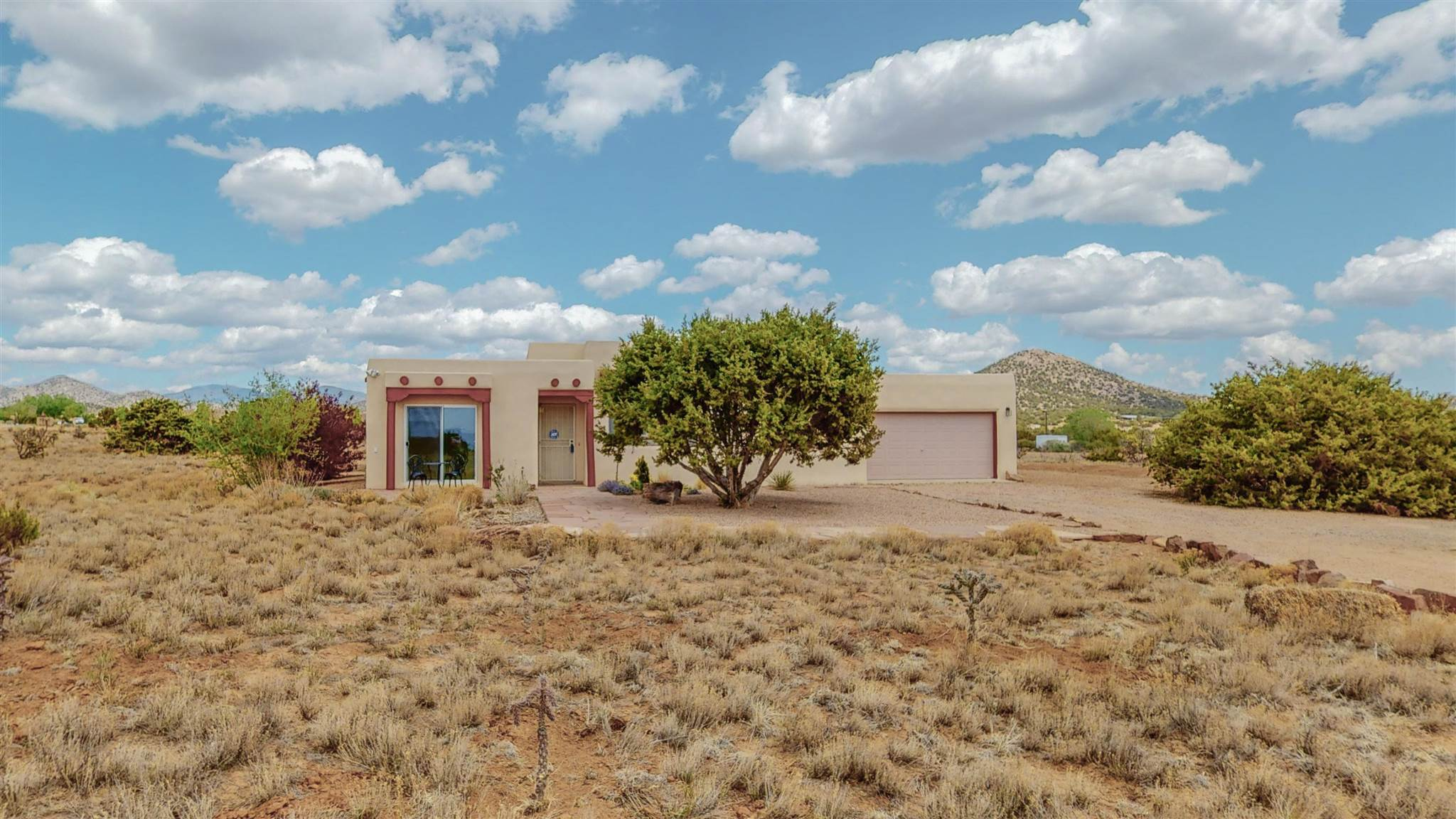 Welcome home! Enjoy the Sangre de Cristo foothills views in this excellent family home on over an acre. This home offers beams, three bedrooms, and two bathrooms, a gas fireplace in the living room, forced heating, and an evaporative cooler and a recent stucco and roof maintenance. Enjoy the outdoors from the spacious, fenced-in, graveled backyard, located a stone's throw from the conveniences of La Tienda and the Agora shopping centers.