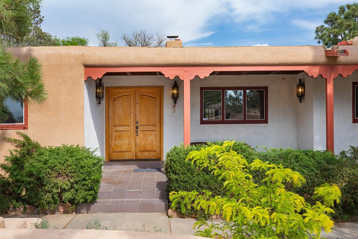 Don't miss your chance to live in such an amazing area.  Are you looking for Santa Fe Charm?  An excellent location, close to downtown, but not to close?  This is your home.  It's large, spacious, at the end of a quiet cul-de-sac and has lovely Santa Fe touches. The house is situated on a large lot with beautiful grounds, sweet views and mature trees.  Home features four bedrooms, three bathrooms an extra den with a bar off living room, a two car garage, and boasts three wood burning fireplaces, split floor plan, ample kitchen cabinets, beamed ceilings and gorgeous kitchen and dining area.  Living room is large and open, it features high wood beamed ceilings, tile flooring and surrounds an inviting wood burning fireplace.  Dining room is next to an open kitchen and offers it's own lovely Kiva wood burning fireplace.  Dining room includes beamed ceilings and wood flooring.  Home wired for security and grounds feature invisible fencing for dogs, lovey front and back porches, drip/sprinkler system and abundant storage.  Location very desirable, close to parks, (the rose park) schools, shopping and downtown. Peaceful and lovely, come see the house and walk the grounds.