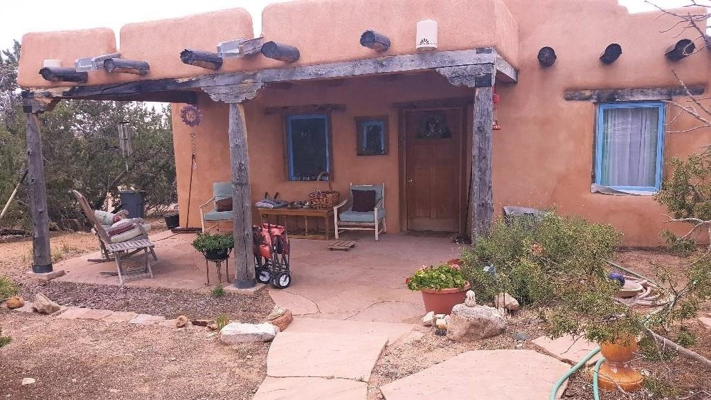 An Adobe rough Gem needing polishing and  attention to deferred maintenance. A flagstone path and colorful portal leads to this adobe home with true Santa Fe Charm. 3-4 bedrooms 1 & 3/4 baths. !1.8 acres with unobstructed views. The homes passive solar design features a huge sunroom, A flexible open floorplan with a generous Kiva fireplace. the large kitchen island welcomes family and friends. Enjoy the morning sun and evening stars from the French doors in the living room and master bedroom. The elegant master bath is a peaceful sanctuary with a jetted tub. In true country style there is an enclosed chicken coop and 2 dog runs designed with safety in mind. The seller is aware of deferred maintenance issue and has reprice accordingly.