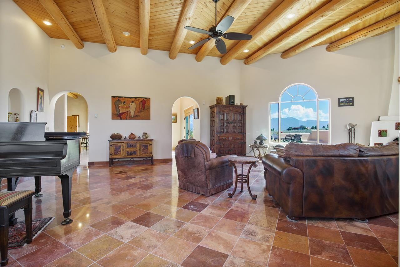 The beauty is in the details. From the private country club location to the imported rojo tile, Viking appliances to the expansive patio for entertaining. Every attribute comes together in this perfectly maintained 3 bed, 2.5 bath, 2 car garage home on 3 acres in Taos Country Club. Custom hand-carved front doors are inviting and set the design tone. Once inside expansive views of Taos Mountain abound from every window. The living room is sun filled and bright. Art commissioned tiles adorn the adobe chimenea fireplace warming the room and the soul when the sun goes down. The gourmet kitchen is enhanced with Viking appliances throughout including a large commercial grade refrigerator. Custom made handcrafted cupboards are an exquisite backdrop to the verde peacock granite countertops. Master bedroom is spacious with fireplace and French doors opening to the sprawling brick patio. Unwind in the Oceania jetted hospital grade tub for two. Relax under the stars in the hot tub nestled just steps off the patio. All bathroom sinks are onyx or marble with custom cabinets and hardware topped with glistening granite. The large brick patio facing Taos Mountain is ideal for outdoor living and entertaining. The garage features an epoxy floor with plenty of space for two vehicles, work area and outdoor toys. Mature gardens and trees surround the home and patio adding to its serenity. Elegance is waiting for you at Taos Country Club.