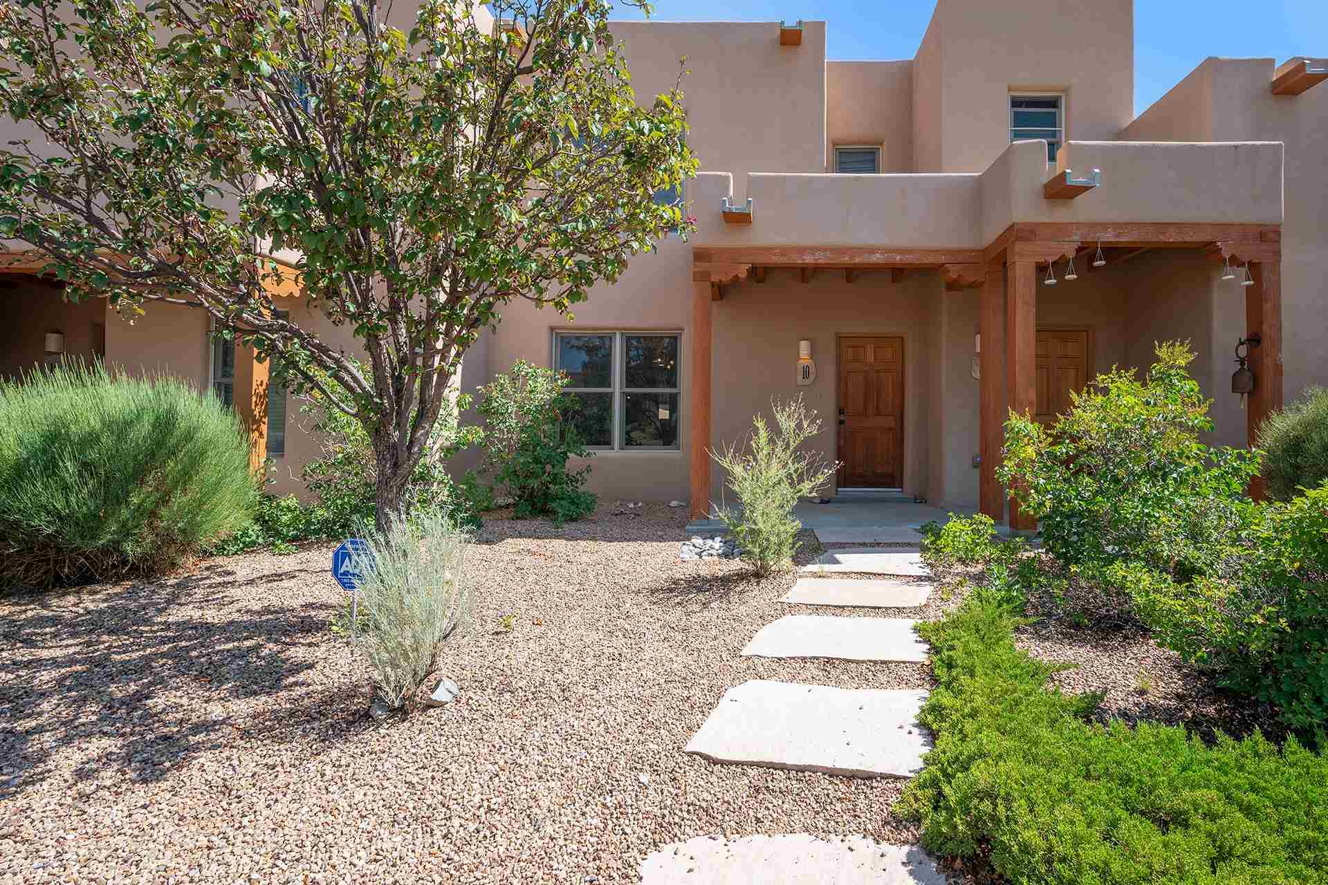 Cute light filled townhouse in sought after Aldea de Santa Fe. Built in 2004, 2 bedroom 1 full and 1 half bath, 1174 sf.  It is privately situated across the from the park and has an open floor plan. The sweet kitchen has the following upgraded appliances: Bosch Dishwasher and kitchen faucet, 2017 and a new garbage disposal, 2021. Additionally there us new stucco in 2019, new treks stairs leading from the courtyard to a private 2 car parking area, 2020; a new Washer Dryer 2019, and a roof refresh in 2019.   This is perfect investment property or starter home. Beautiful views of sunsets from the front upstairs bedroom. From the kitchen into the back yard is a private courtyard with a mature trees including an apple tree tree. This area is perfect for private outdoor dining. Aldea has high speed internet access, 13 miles of walking trails, tennis, pickle ball and basketball court. On the plaza is the community center that  you get free use of for your events. Here, you will also find a coffee shop and Dr's office.