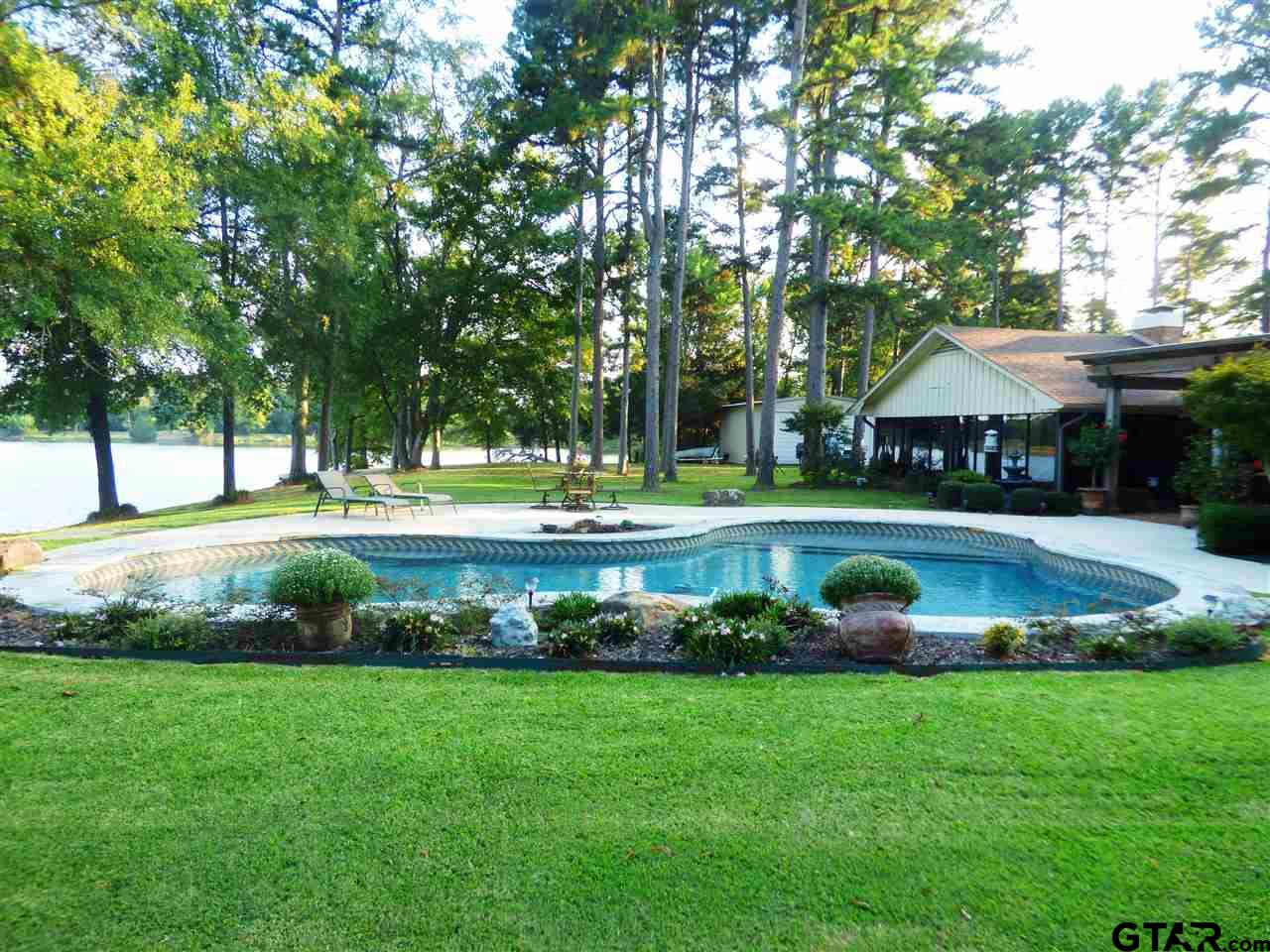 ONE OF A KIND, PRISTINE LAKE FRONT PROPERTY  ONLY A FEW MINUTES FROM TOWN   THIS APPROXIMATE 3300 SQUARE FOOT EXQUISITE HOME SITS ON A 1.6 ACRE PENINSULA WITH FABULOUS VIEWS OF LAKE TANKERSLEY.  IF YOU AND YOUR FAMILY ENJOY ENTERTAINING OR JUST RELAXING AT YOUR OWN RETREAT, THIS IS THE PLACE FOR YOU.  YOU WOULD ENJOY THE HOME WITH 2 LIVING AREAS DIVIDED BY A TWO SIDED  FIREPLACE.  WINDOWS THAT BRING THE OUTSIDE INSIDE AND OVERLOOK THE BEAUTIFUL LAKE AND THE SALTWATER POOL.  THIS BEAUTIFUL PLACE COULD BE CALLED AN OASIS WITH THE OUTDOOR PERGOLA AND KITCHEN/BAR. DID I MENTION THE 1100 SQ FT SHOP WITH BAY DOORS AND THE PROPERTY BOASTS OF 2 WELLS, SPRINKLER SYSTEM, A SECURITY GATE.  TOP OF THE LINE APPLIANCES (PROPANE TANK JUST FOR GAS COOKTOP AND FIREPLACE.  CALL FOR YOUR PERSONAL TOUR OF THIS WATERFRONT RETREAT.