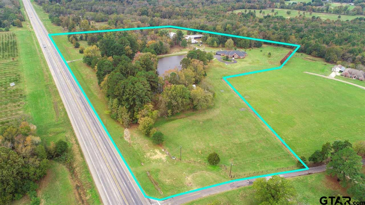 Countryside estate on over 20 acres of improved property with 7 acres of income potential vineyard. Drive up the luminous driveway to this gorgeous 5100 square foot home featuring 4 bedrooms, 5.5 baths, and 2 vehicle circular carport. The chef's kitchen features gas appliances, and the homes fireplace is also gas. House and deep well are backed up by a gas generator,  with Co-op water also featured. Outside you'll find a 75x75 steel truss barn with 7 stalls with Nelson waterers in each stall and enclosed tack room. 20x25 new chicken coop, fenced and cross fenced with 3 separate grazing areas all featuring automatic waters. Second home on the property has been completely renovated and features a single car garage. Enjoy the panoramic views of the fully stocked pond (catfish, crappie, and bass) from the magnificent glass encased gazebo. No expense was spared in this immaculate, close to town, ranch home.