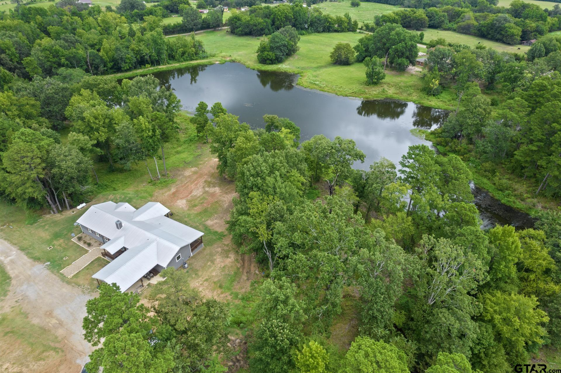 Country Oasis! Opportunities like this don't come often. Charm, character, and attention to detail abound in this custom built pier and beam home. With over 800 sqft of porches, perfectly situated to take every stunning view of the 4+ acre natural spring fed lake, you will be hard pressed to find this kind of peace and serenity elsewhere. The open concept living space with grand rock fireplace, kitchen any chef would be at home in with leather finish granite countertops and stainless steel appliances, and dining room with the perfect waterview make this beautiful home the perfect place for entertaining! Dual primary suites make this a truly unique build in its own right. While one features its own HVAC and on demand water heater making it the perfect in-law-suite. The entire back of the home has stunning views of the manicured property and a gorgeous private lake. Call today to schedule your private showing!