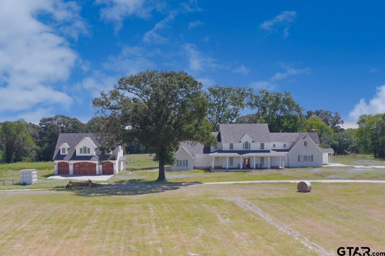 This is a unique chance to own paradise in East Texas!  Just north of idyllic Hainesville and a 45 minute drive to Tyler, over 182 acres of highly improved pastureland with a European-inspired modern farmhouse is waiting for your personal touch.  This land is multi-use capable and ready for agriculture and livestock projects or could be used as incredible hunting and recreational grounds. A large lake, stocked with bass, provides fishing and irrigation for pastures and is serviced through a state-of-the-art pumphouse.  A covered pier with fans is large enough for big gatherings, and a separate pier on the other side of the lake offers more fishing options.  A metal hayshed and a large chicken coop are near the pastures. Enter the property through custom metal gates and a stop at the exquisite gatekeeper's cottage, with full bath and kitchenette.  The luxurious finishes in this cottage are continued in the showroom worthy garage and living spaces.  This four-car garage features custom cabinetry and sealed concrete floors and offers office space and guest quarters upstairs.  Two exquisite full baths have cedar shiplap, penny tile, and granite counters, and custom trim and ceilings are in every room.  The property's main residence is sheetrocked and partially trimmed and will be luxurious modern farmhouse living at its finest!  The home and sweeping front porch face west for those breathtaking Texas sunsets, while a covered back porch will keep you cozy to greet the day's morning sunrise.  Walk through the front door and be greeted by Texas-sized windows and a Texas limestone fireplace feature wall.  The master suite, including a sitting area and bathroom retreat with his and hers closets, is on the main floor.  Formal dining, formal living, an office, media room, game or poker area, and safe room are slated for the current floor plan, including three guest bedrooms and two guest baths upstairs.  Don't miss your chance to own this versatile and stunning property!!