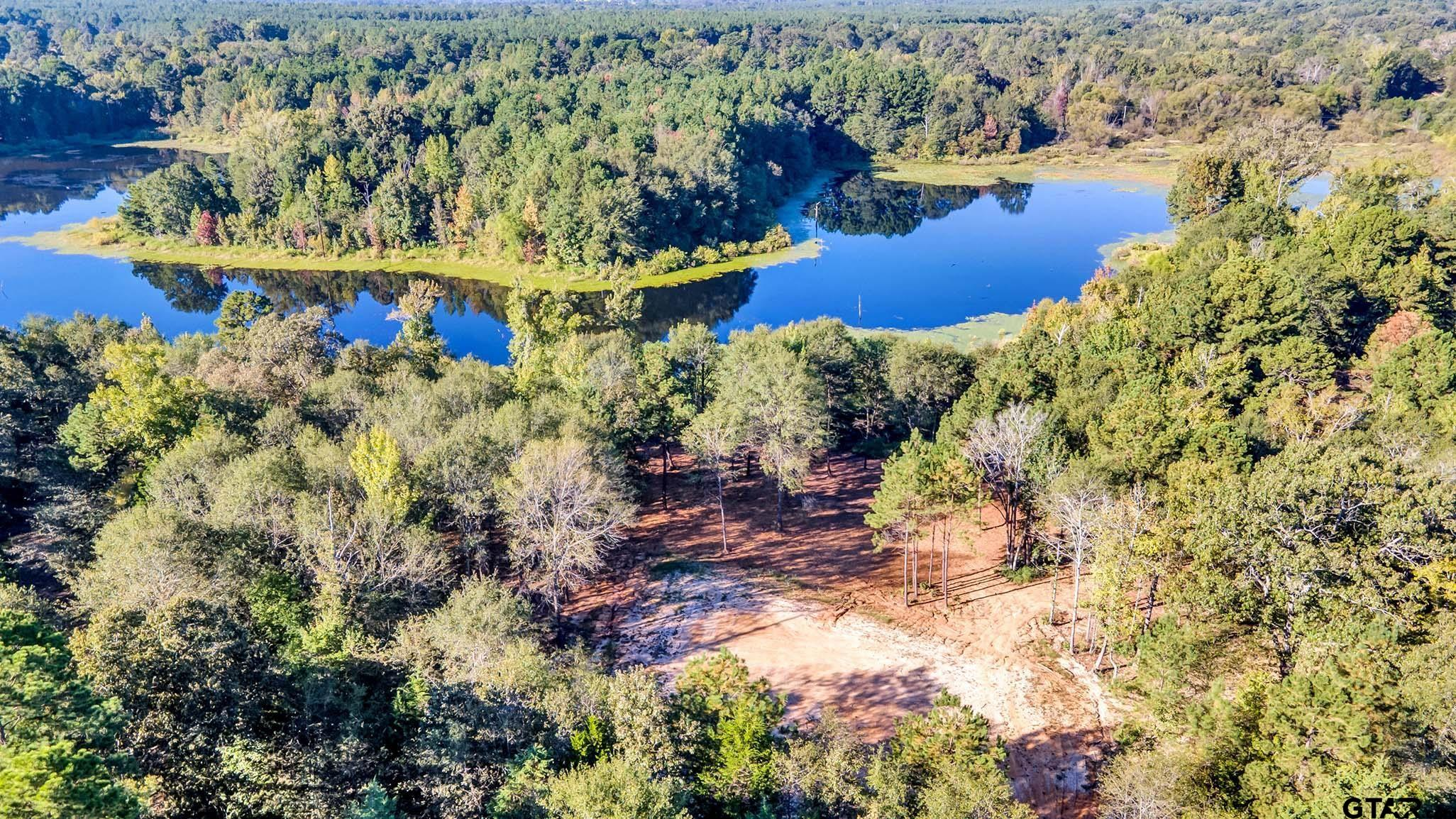 Beautiful setting....Approximately 41.5 wooded acres of TIMBER...w/ access to a shared PRIVATE LAKE. This lake is over 20 feet in depth and measures approximately 29 acres. Apx 215 yards of water frontage! Owner has already established road into the property, house pad, & an amazing view of the lake!!! Imagine the possibilities with this piece of paradise!  What an amazing opportunity to purchase an income producing property that also has an array of wildlife & lake! A hunters paradise...deer, duck, hogs, squirrels, fishing, AND MORE!! Call today!