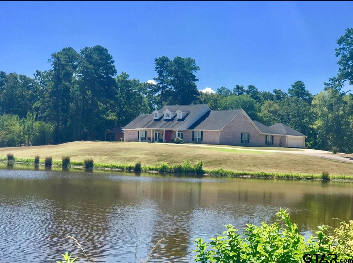 Beautiful custom brick home surrounded by woods overlooking a gorgeous private lake on 5 +/- acres. This 4 bedroom, 3 bath, 2 car garage has a study, formal dining, utility room w/sink, and 2 living areas. There are 2 central units (one is new), gas log fireplace, 2 hot water heaters (one is new), and a new roof. The master has a huge walk in closet, double sinks with separate jacuzzi tub & shower. The kitchen has an island, a new electric drop in stove, new microwave, and new dishwasher. There are wood floors, carpet, tile and vinyl.